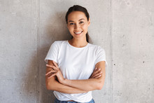 Cheerful Young Asian Woman Standing With Arms Folded