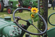 Plastic Sunflower On The Steering Wheel Of An Old Tractor At A Farm Exhibition