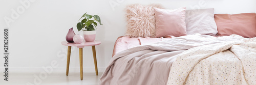 Fotografie, Obraz Real photo of a small table with a plant standing next to a bed with pink beddin