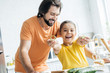 father and daughter having fun at kitchen while cooking