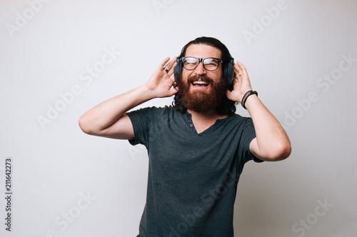 Spoed Foto op Canvas Muziekwinkel Young bearded man wearing glasses smiling at the camera and enjoying music through the headphones.