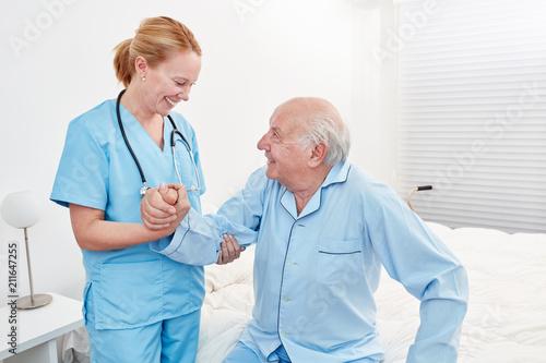 Fotografie, Tablou Weibliche Pflegekraft hilft Senior beim Aufstehen