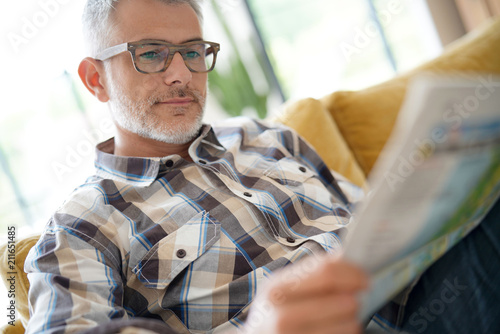 Middle-aged man in kitchen reading newspaper Fototapete