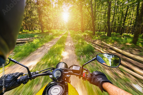 POV shot of young man riding on a motorcycle. motorcycle tour journey in the forest. copyspace for your individual text.