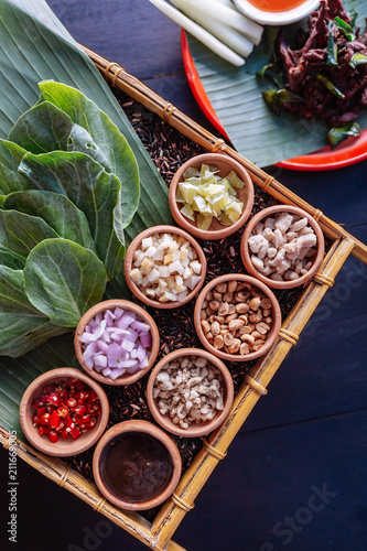 """Thai appetizer called """"Miang Kham"""", some of nutritious snack wrapped in leaves with a sweet and salty sauce."""