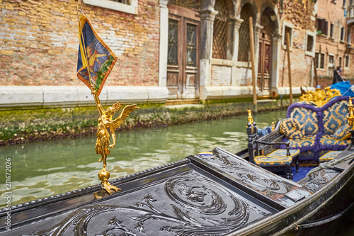 Papiers peints Gondoles Golden Figure with wings and Flag of Venice on Gondola in Venice