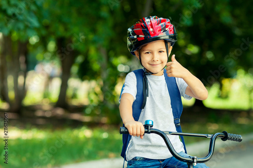 Little boy learns to ride a bike in the park near the home. Kid shows the thumbs up on bicycle. Happy smiling child in helmet riding a cycling.