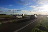 Samochody osobowe i policyjny radiowóz na drodze ekspresowej w promieniach zachodzącego słońca.