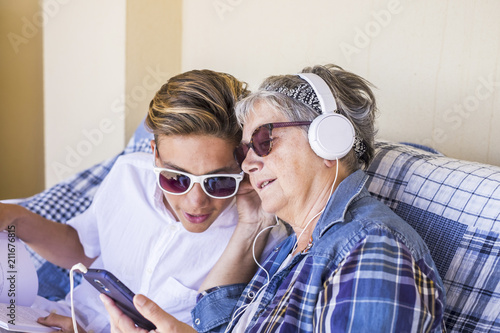 grandmother and nephew teenager spent time together outdoor on the terrace at home listening music with the modern player smartphone and earphone Tapéta, Fotótapéta