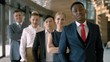 Portrait of handsome black business man with four employees in the business hall