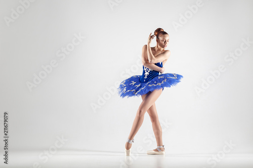 Fotografie, Obraz  Young beautiful ballerina with bun collected hair wearing blue dress and pointe