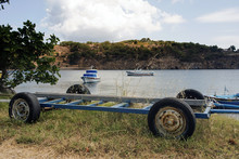 A Boat Trailer And Fishing Boats In The Beach In The Island Of Patmos, Greece In Summer Time