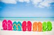 colorful flip flop on sandy beach, green sea and blue sky background for summer holiday and vacation concept.