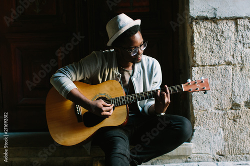African musician playing guitar in the city - 211692812