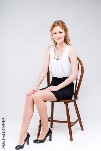 eb911ddefab1 Young beautiful woman with long red, curly hair sitting on a wooden chair on  a white background in the studio. Dressed in a white blouse with a short  sleeve ...