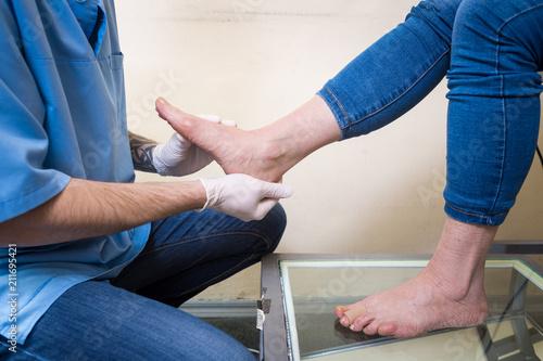 Fotografía  The hands of a young man doctor orthopedist conducts diagnostics, foot foot test