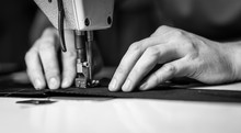 A Man At Work On A Sewing Machine. Without A Face.