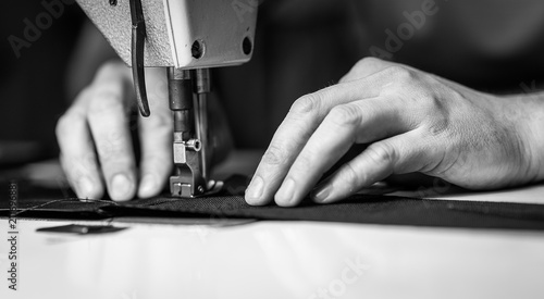 Fototapeta a man at work on a sewing machine. without a face.