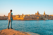 Young Man Standing On The Edge Of The Cliff Watching Valletta City Skyline On Malta.