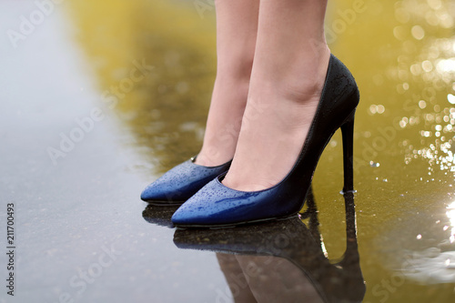 Female feet in shoes on wet asphalt in the rain