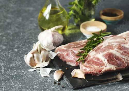 Staande foto Vlees Raw pork meat for grill with ingredients for cooking, dark background.