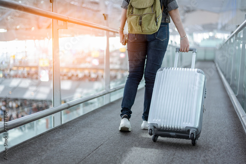 Obraz na plátně Close up lower body of woman traveler with luggage suitcase going to around the world by plane