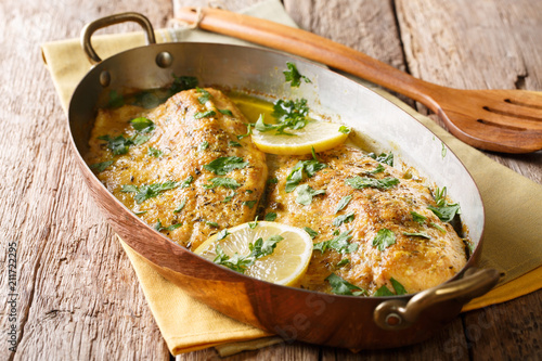 Served baked trout fillets with garlic butter sauce, lemon and parsley in a copper pan. Italian food. horizontal
