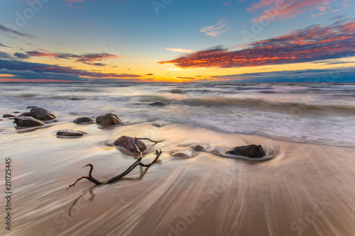 Foto op Aluminium Zalm sunset over the sea beach in Poland, waves dynamically breaking into the beach