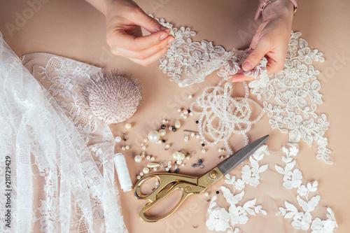 Foto close-up hands of woman seamstress tailor ( dressmaker) designer wedding dress s
