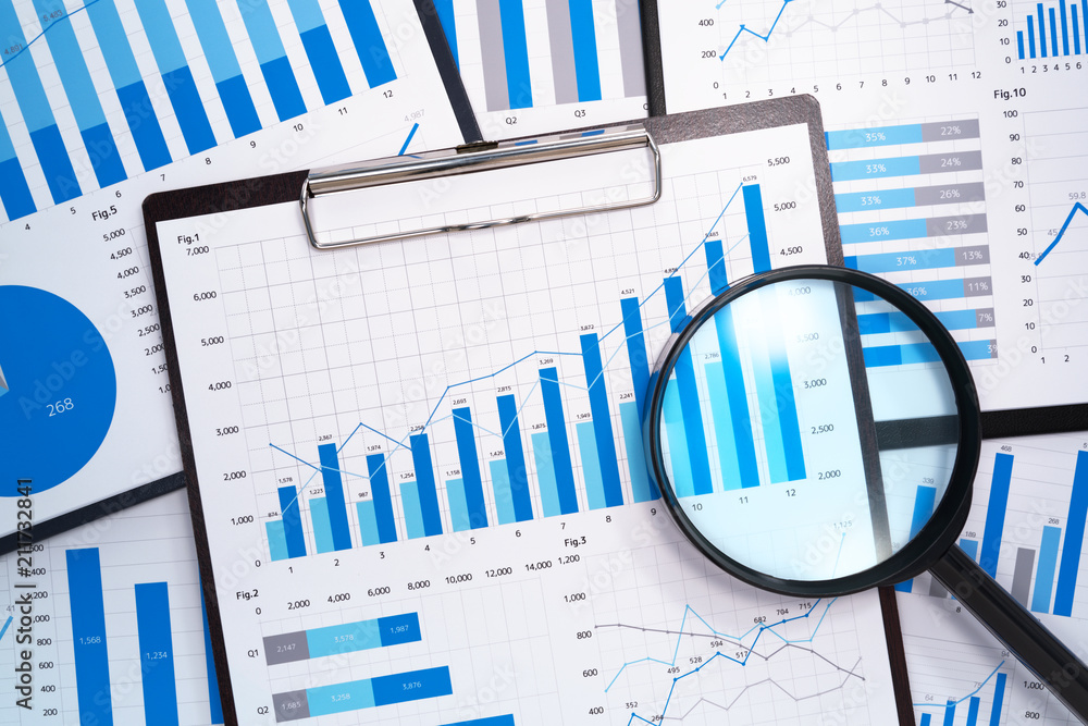 Fototapeta Analyzing and gathering statistical data. Growth charts. Many business reports and magnifying glass.
