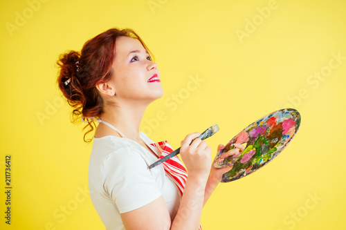Fotografia  portrait of a beautiful artist in an apron holding a palette and brush on a yellow background in the studio