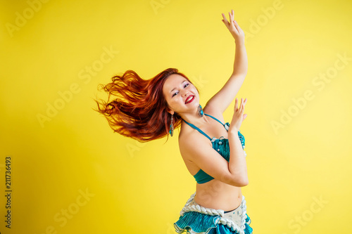 Fotografie, Obraz  beautiful red-haired woman dancing oriental belly dance in blue suit on yellow b