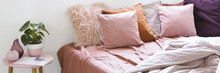 Real Photo Of A Large Bed With Pink Bedding And Pillows Standing Next To A Small Table With A Plant In Bedroom Interior