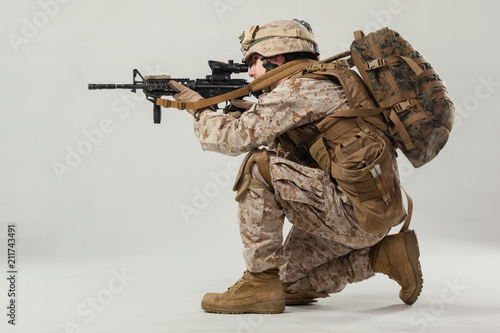 Soldier in camouflage holding rifle Fototapete