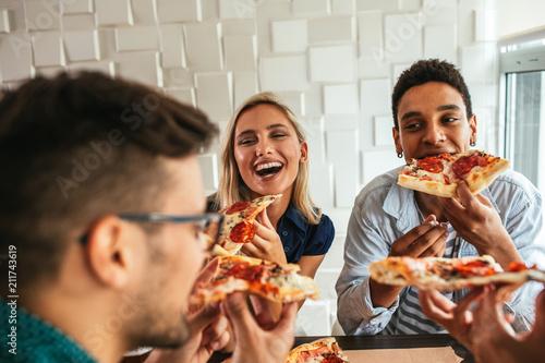 Fotografie, Obraz  Grabbing a slice of pizza with friends