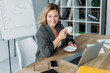attractive businesswoman sitting with cup of coffee at table in office