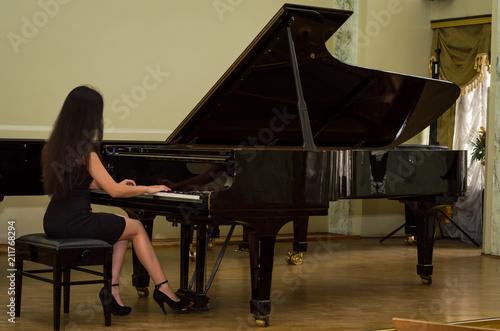 Obraz na płótnie Young charming brunette girl playing the piano
