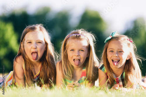 Three little girls sticking their tongues out Fototapeta