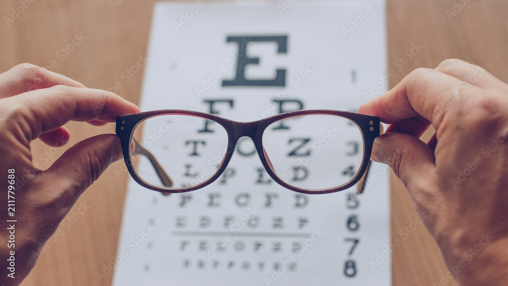 Fototapety, obrazy: Hands holding sight glasses in front of optician sight chart. Eyesight optician concept