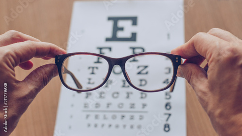 Photo  Hands holding sight glasses in front of optician sight chart