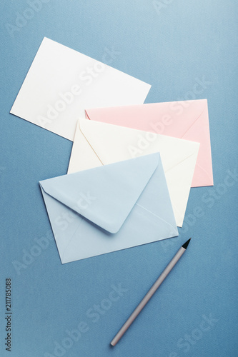 Fotomural Group of colorful envelopes on blue table with empty card