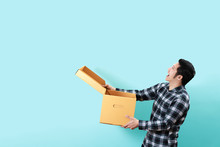 Side View Of Happy Customer Asian Man Smiling Opening And Holding Box Looking Up To Copy Space Above With Isolated Blue Background Feeling Excited And Satisfaction. Ordering Or Buying Concept Design.