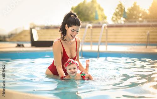 Photo  Cute mom teaching her daughter how to swim