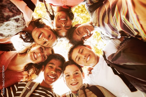 Portrait of smiling school kids forming a huddle in campus Canvas Print