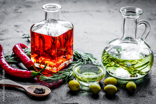 Fototapeta Bottles with chili and olive oils and herbs on stone background obraz