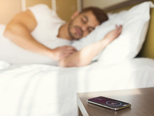 Man Sleeping In Bed While Hearing Alarm Clock