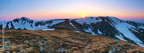 In de dag Cappuccino Panoramic view of the picks of high mountains covered with snow, meadow with the rocks, amazing sunrise