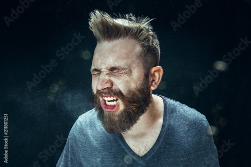 Young handsome man with beard sneezing, studio portrait Fototapete