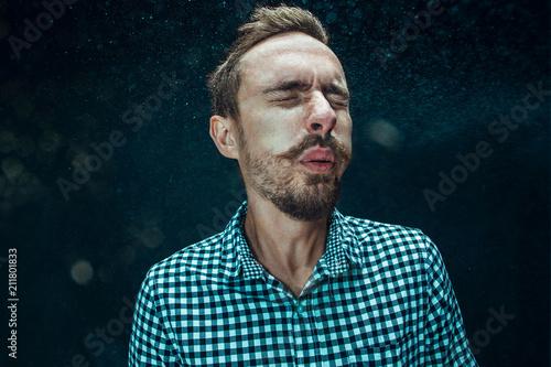 Young handsome man with beard sneezing, studio portrait Wallpaper Mural