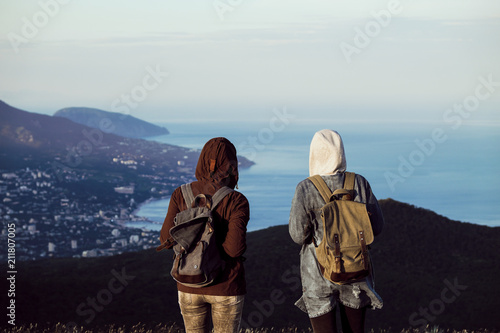 Two girls traveler stand on the top of the mountain, look down, jump, rejoice and dance Canvas Print